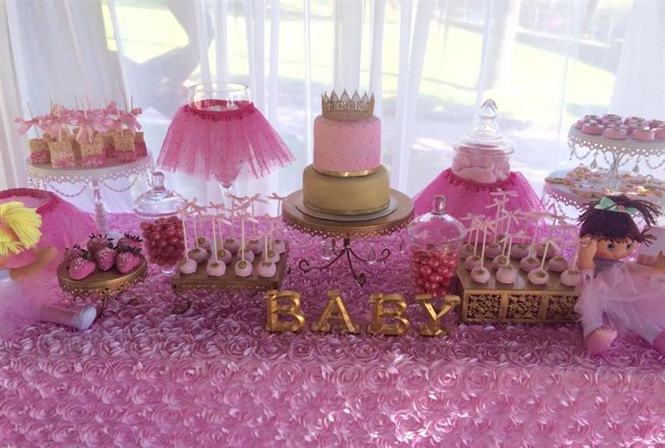 A grand baby shower cake for a girl with pink tutus and dolls