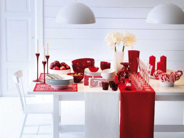 A holiday table decked up with multiple red and white accessories