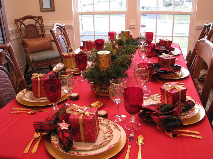 A lavish Christmas table setting with cute gift boxes set over dinner plates