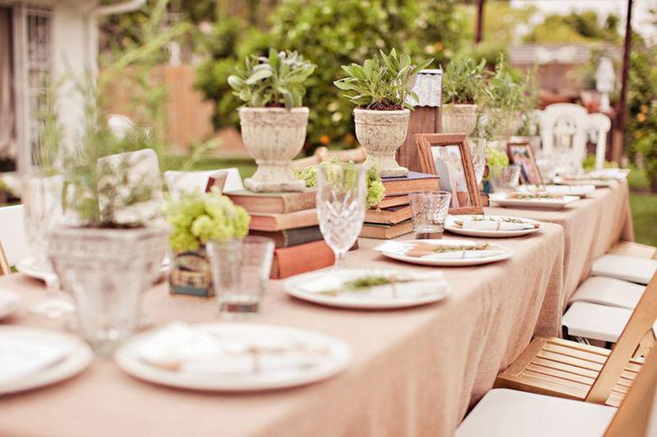 A natural themed outdoor bridal shower table styled with plants and books