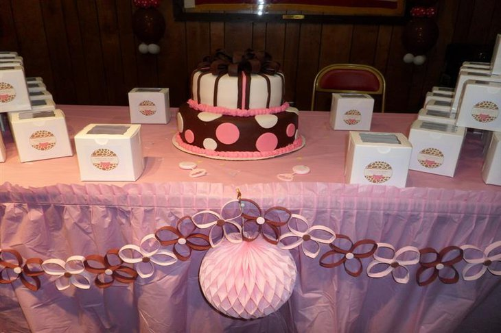 A pink baby shower cake for a baby girl accentuated with brown ribbons