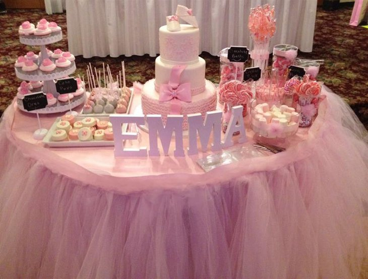 A pink baby shower cake themed around the tutus for ballerinas