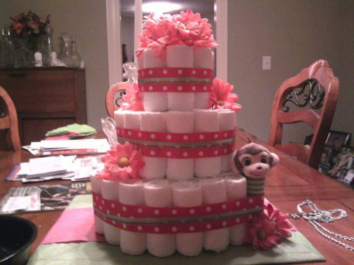 A pink baby shower diaper cake decorated with pink ribbons