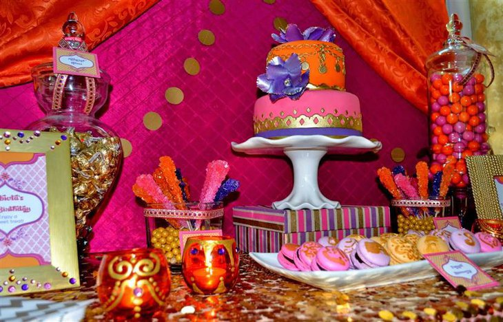 A pristine orange and pink baby shower cake with royal decorations