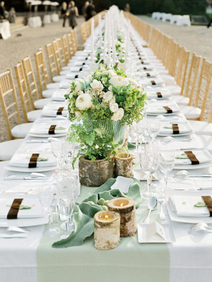 A romantic outdoor country wedding table embellished with wooden candle holders and flowers