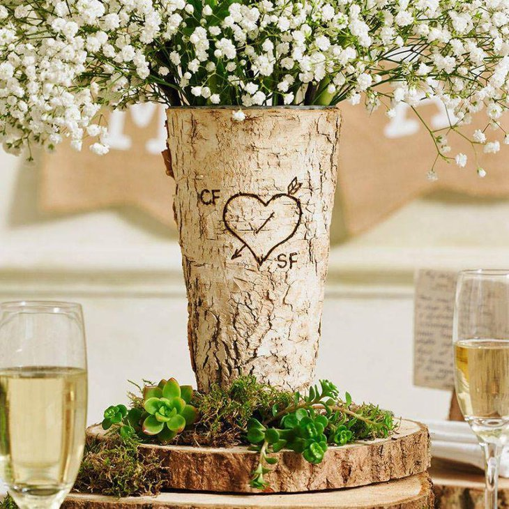 A rustic birchwood vase with flowers on this country wedding table