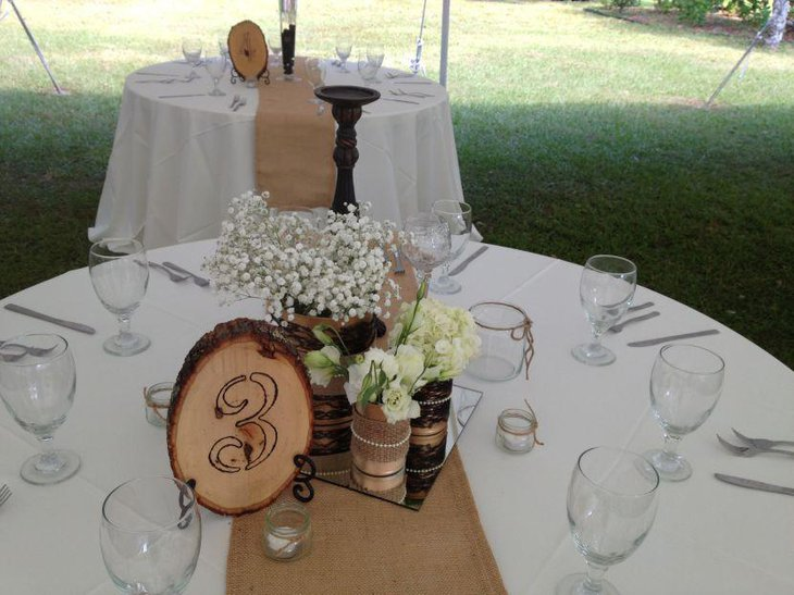 A stylish and wam looking country wedding table decorated with burlap accents
