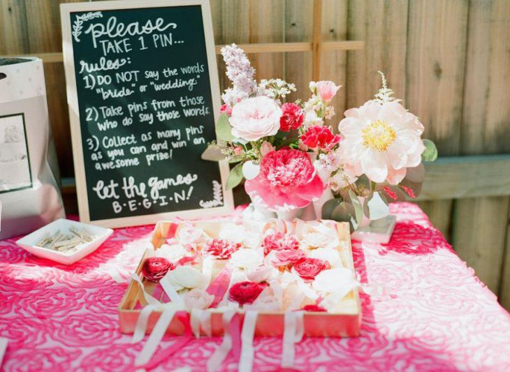 Adorable pink flowers and tablecloth decor on a bridal shower table