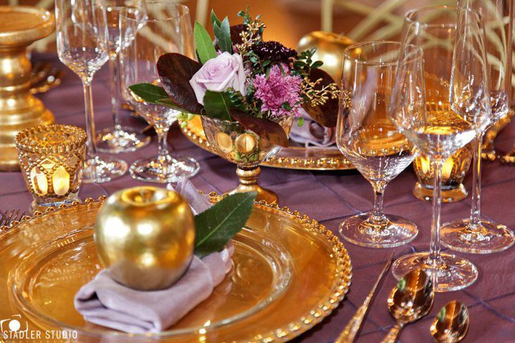 Adult birthday party dinner table with golden plates and decorative apples