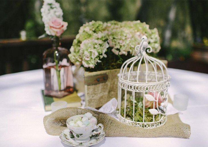 Alluring floral accented birdcage centerpiece on wedding table 1