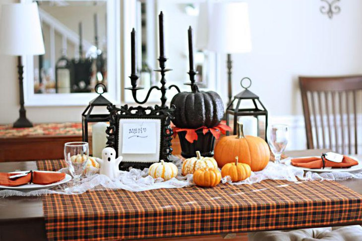 Amazing black and orange pumpkins as Halloween table decorations along with black candles