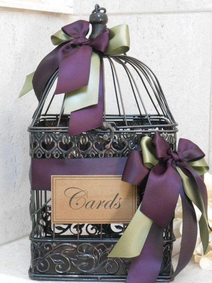 Amazing black birdcage wedding table centerpiece with purple ribbons