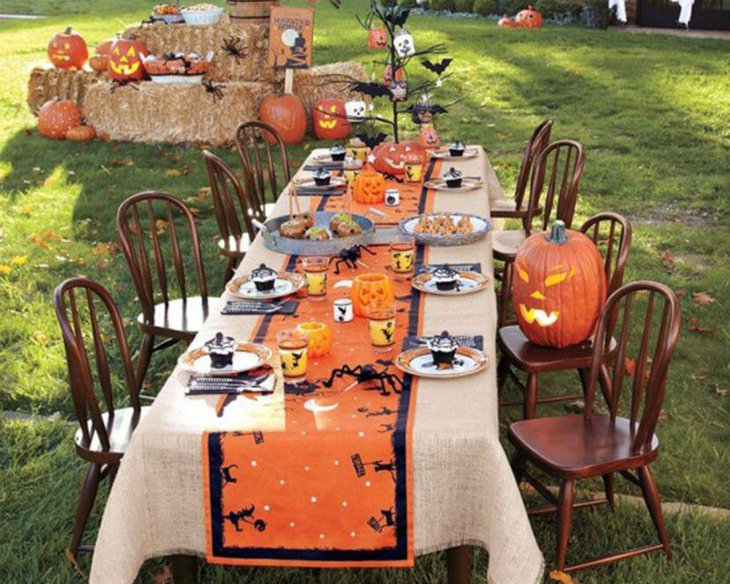 Amazing outdoor Halloween table decor with orange runner and pumpkin