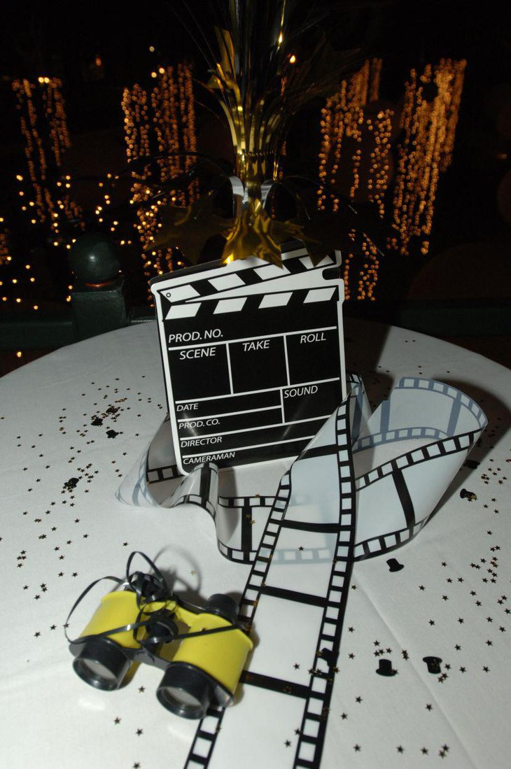 An oversized clapboard is placed on a party table as a main centerpiece