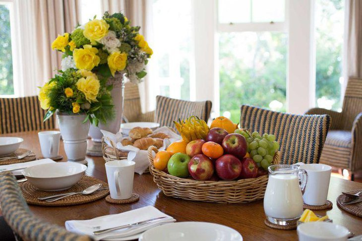 Appealing breakfast table decor with yellow flowers and fruit basket