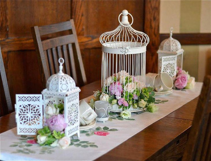 Appealing white iron birdcage centerpiece with flowers