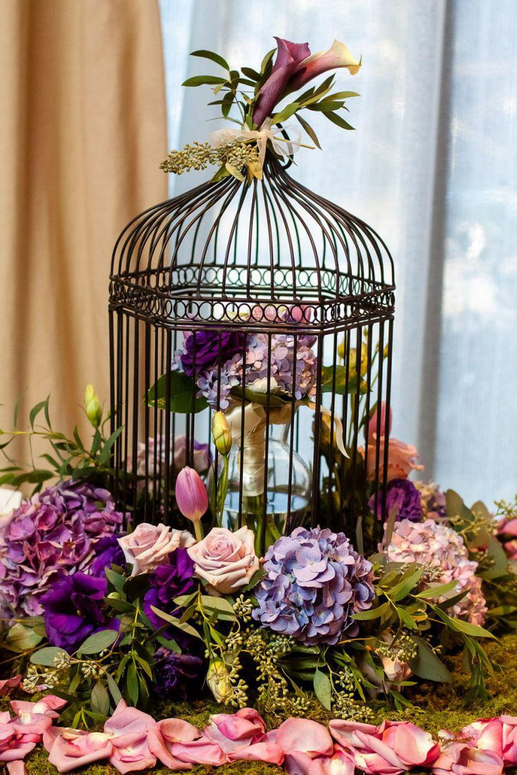 Astonishing birdcage centerpiece with purple floral accents