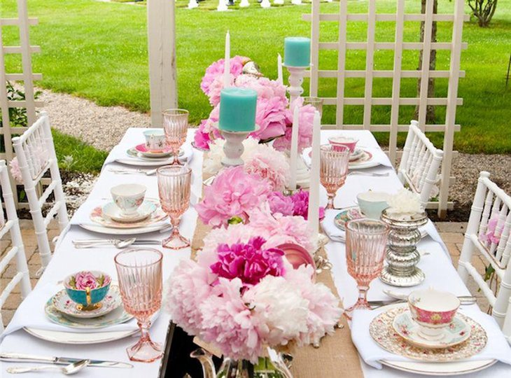 Astonishing party table setting with pink floral bunches and blue candles