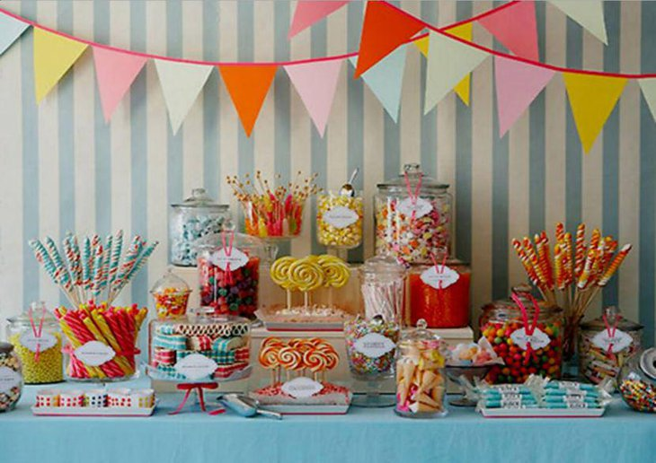 Attractive dessert table decorated with candies in glass jars