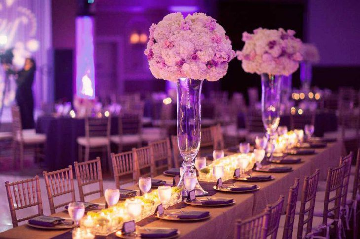 Attractive wedding table decor with tall purple floral centerpiece