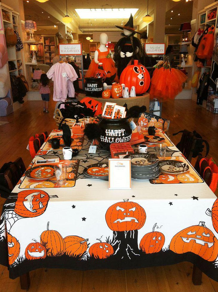 Awesome kids Halloween party table decor with cute pumpkin tablecloth and plates