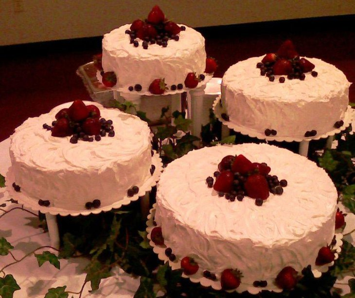 Awesome retirement table decor with white cakes topped with strawberries