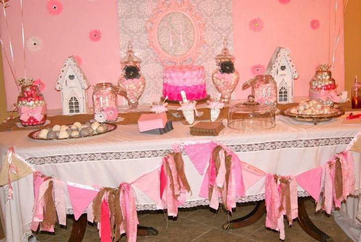 Baby shower dessert table idea with pink accents on cake bows and candies