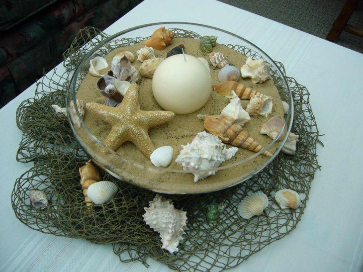 Beach party table decor with a sand bowl filled with star fish candle and shells
