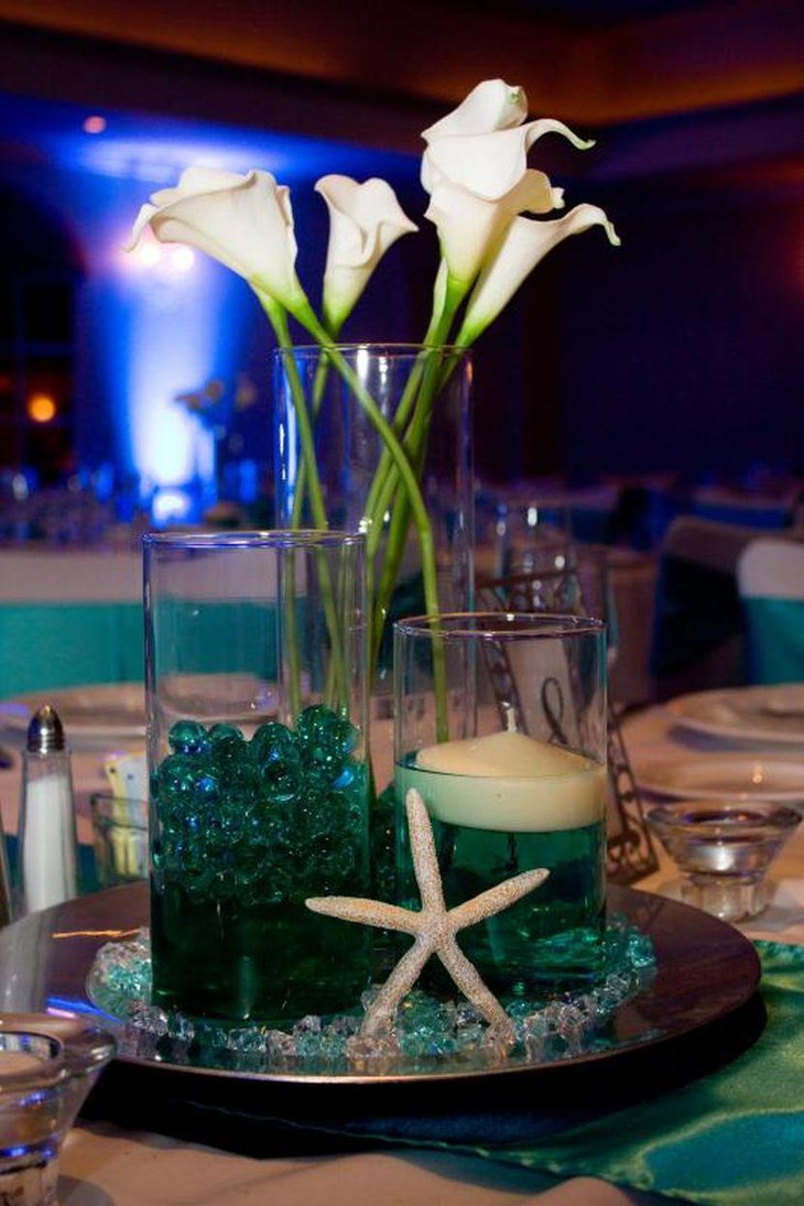 Beach themed wedding table setting with lily arrangement