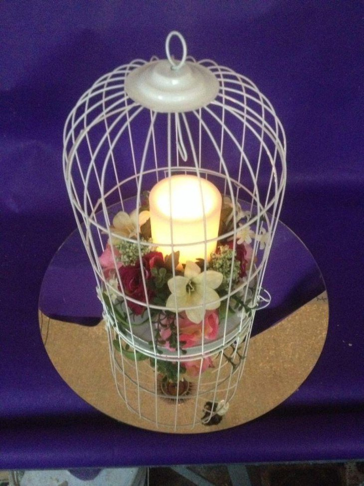 Beautiful birdcage centerpiece with candle and flowers