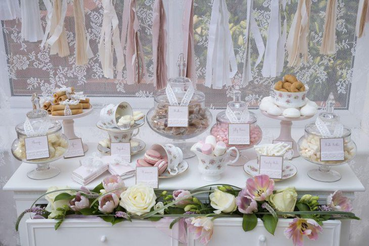 Beautiful dessert table arrangement with glass jars and ceramic cups