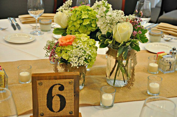 Beautiful flower arrangement in mason jars for wedding table