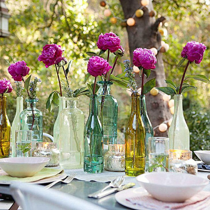 Beautiful garden party table decor with coloured bottles and pink roses