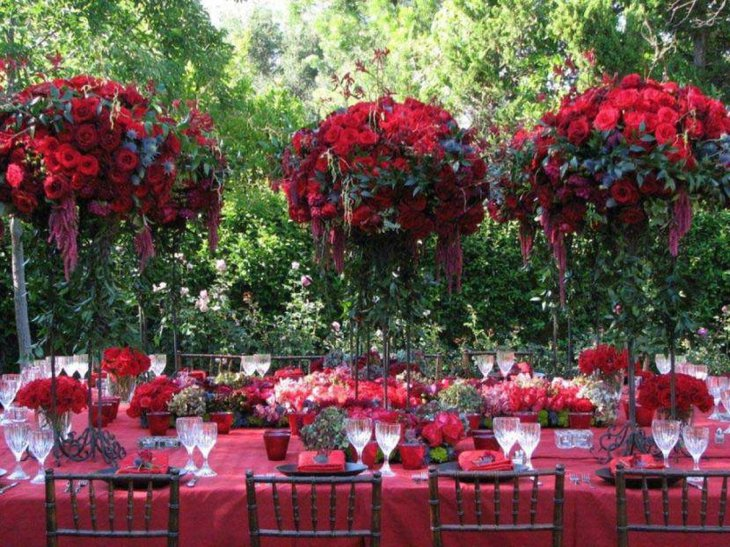 Beautiful red themed summer party table decoration with red flower bouquets