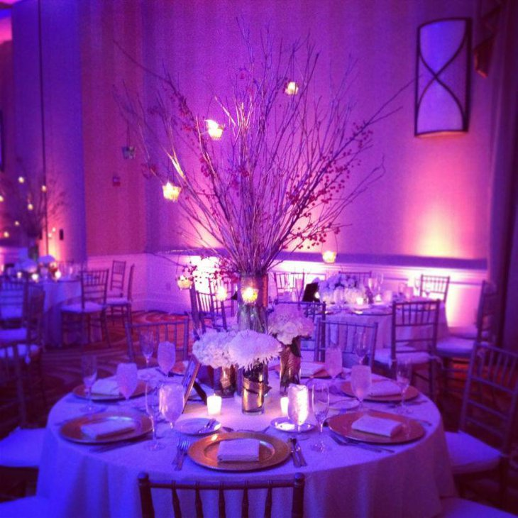 Beautiful spray painted branches with light bulbs as party table centerpiece