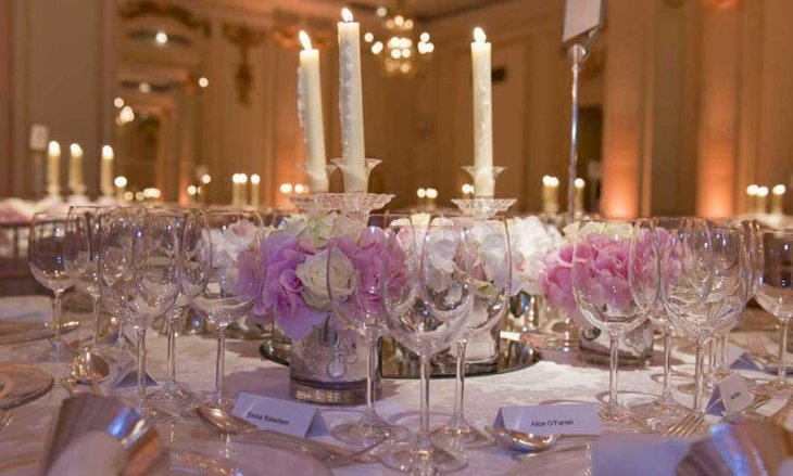 Beautiful wedding reception table decor with pink and white roses and candles