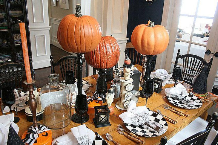 Big pumpkins on black curvy holders as Halloween table centerpieces