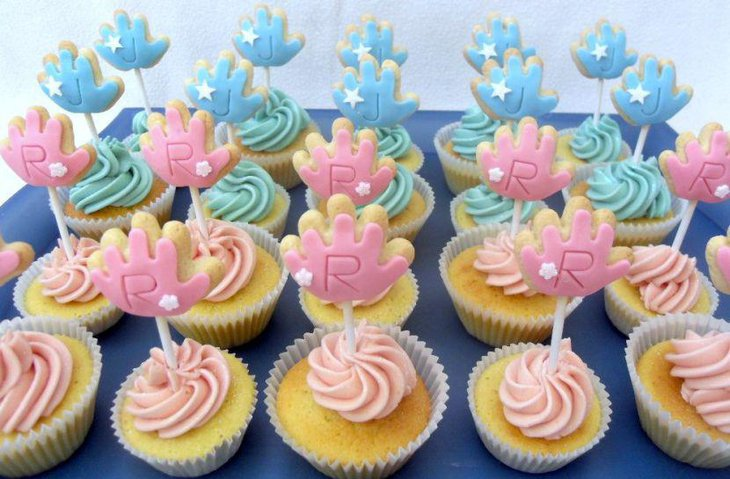 Blue and pink themed twin baby shower cupcake decor on table