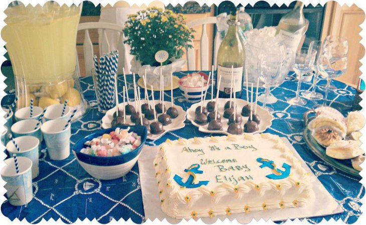 Blue and white anchor cake centerpiece on nautical themed baby shower table