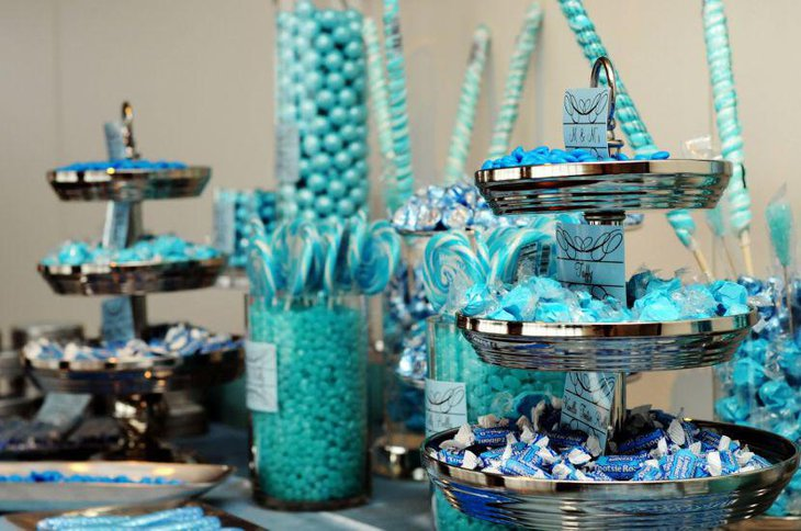 Blue inspired baby shower candy buffet table decor using decanters filled with blue candies