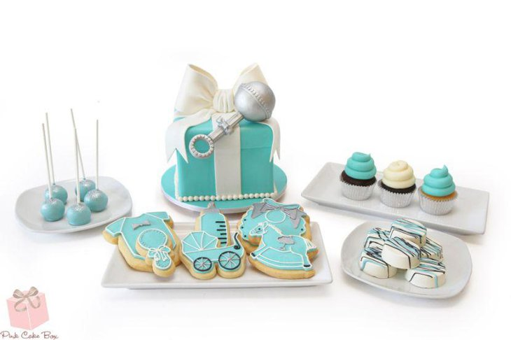 Blue themed baby shower candy table with blue cake and cookies