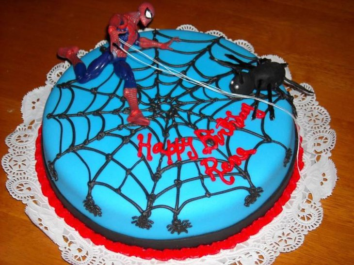 Blue Webbed Spiderman Cake With Spiderman Running On Top Of It