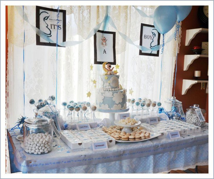 Boy baby shower dessert table decor with blue balloons cake and lollipops