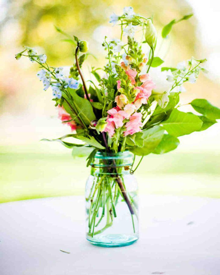 Bunch of flowers in glass jar for table decor