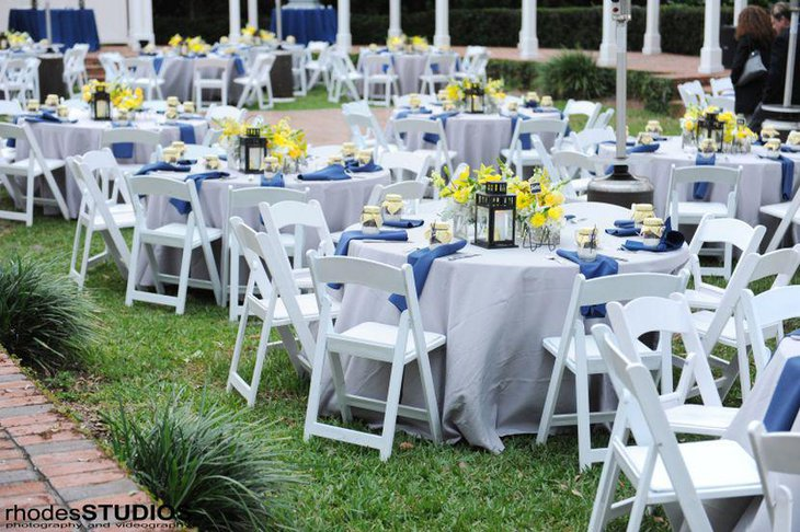 Chic garden party table decor with yellow flowers and blue napkins