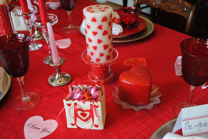 Chic red heart candle and tablecloth decor on Valentines table
