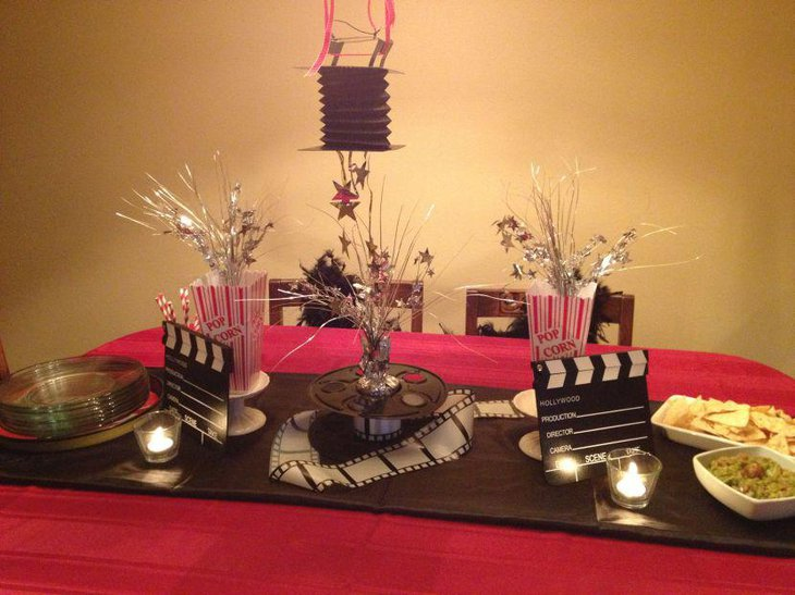 Clapboard and movie print reel displayed as party table centerpieces