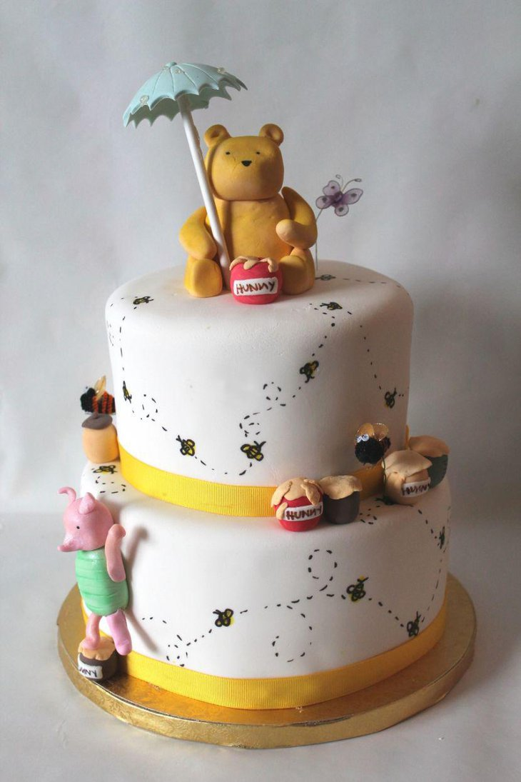 Classic Winnie The Pooh baby shower cake decor with yellow ribbons and Pooh bear
