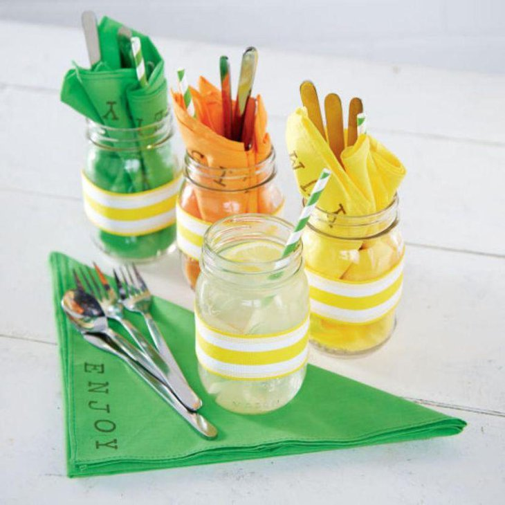 Colorful cutlery holding mason jars for wedding table