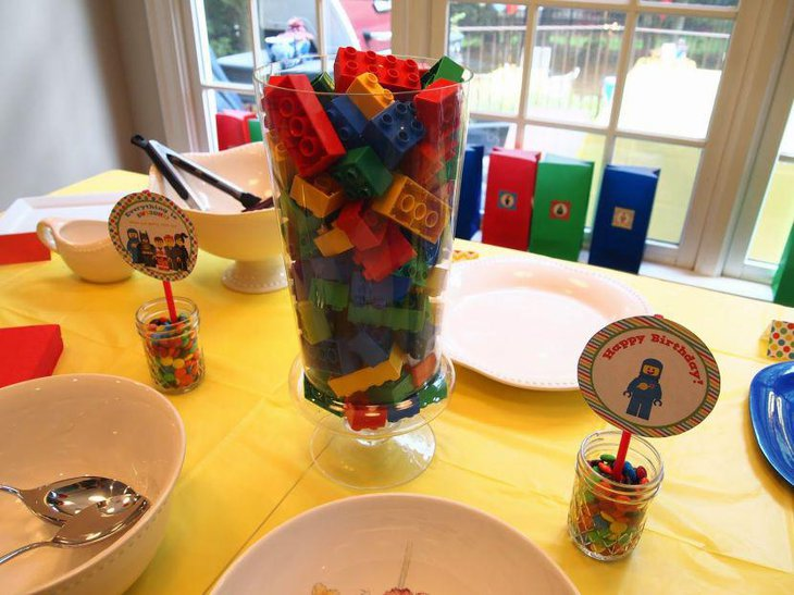 Colourful jar filled with Lego blocks as birthday table centerpiece